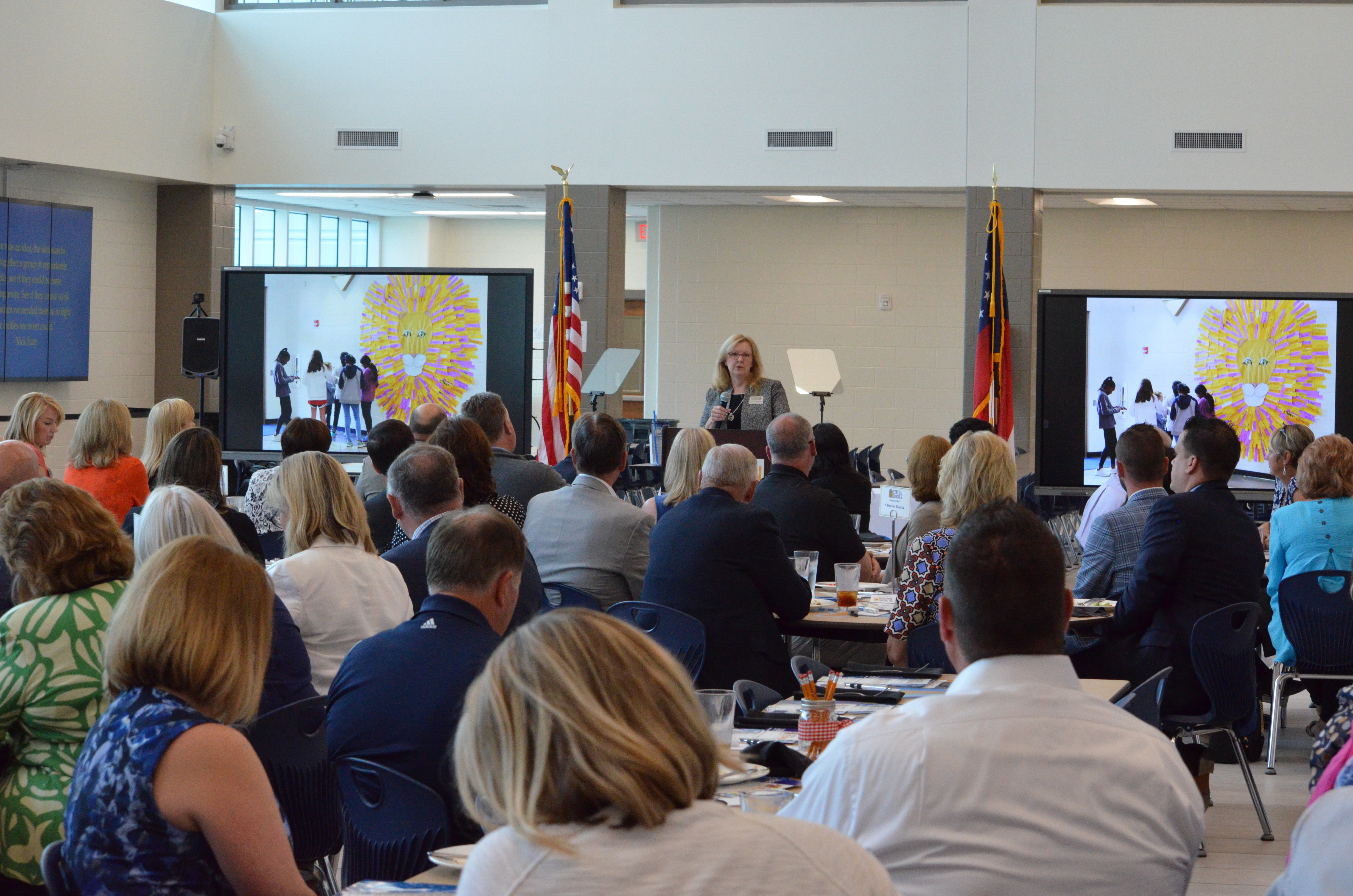 Attendees of State of the Schools listen to Kristen Morrssey present on the school year.